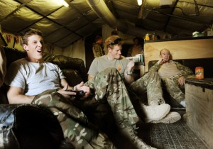 Prince Harry enjoys some down time playing video games with his fellow Apache helicopter crew members.