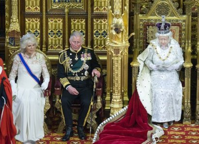 The Duchess of Cornwall and the Prince of Wales sit beside the Queen as she reads her speech during the 2013 State Opening of Parliament.